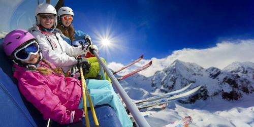 Vrouw met dochters in skilift